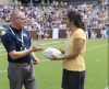 Coach Geoff Collins hands Dr. Jennifer Singh a signed game ball during the GT v. Citadel football game.